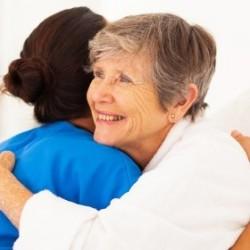happy elderly woman hugging caregiver