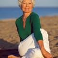 Senior woman enjoying yoga on the beach