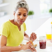Mature Woman Eating Breakfast And Reading Newspaper